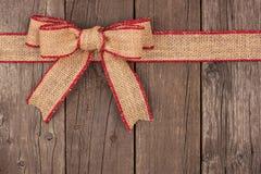 粗麻布圣诞节弓和丝带顶面边界在木头 库存照片