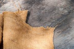 粗麻布黑森州袋装在木背景 库存图片