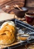 粗暴小圆面包用在烹调期间的桂香,在未加工的面团涂黄油 免版税库存图片