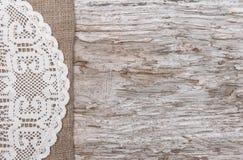 粗麻布和有花边的布料毗邻的老木头 免版税库存图片