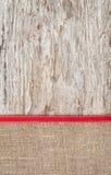 粗麻布和红色丝带毗邻的老木头 免版税库存照片