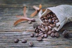 粗麻布大袋在老木背景的咖啡豆 图库摄影