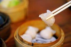 粤式点心或Har Gow饺子由从一个竹火轮篮子的筷子采摘 关闭Ha Gow,普遍的开胃菜 库存照片