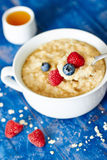 粥用莓果和蜂蜜在匙子 图库摄影