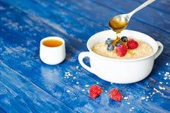 粥用莓果和蜂蜜在桌上 库存照片