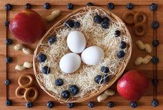 粮食构成用在篮子、莓果和苹果的鸡蛋 免版税图库摄影
