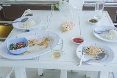 粮食残滓在白色塑料盘的在木桌上 库存照片