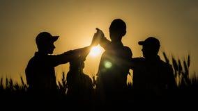 精力充沛的年轻人队做在一块美丽如画的麦田的高五马克在日落 库存图片