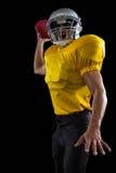 精力充沛的美国橄榄球运动员在一只手上的拿着一个球 免版税库存照片