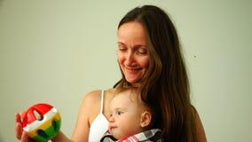 精力充沛,愉快和快乐的婴孩是playingthe孩子采取从人的手的一个玩具坐妈咪` s膝部 股票录像
