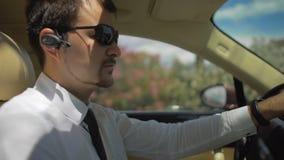 精华出租汽车的汽车夫驾驶汽车在度假村和谈话与乘客 股票视频