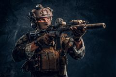 精华单位,拿着有激光的伪装制服的特种部队战士一杆攻击步枪看见并且瞄准 免版税图库摄影