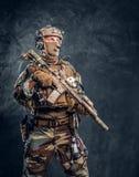 精华单位,摆在与攻击步枪的伪装制服的特种部队战士 免版税库存照片