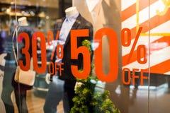 精品店和销售标志 商店在岗位的窗口显示关于销售 五十百分比折扣的公告在a的 免版税库存图片