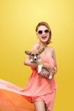 精密春天礼服的美丽的年轻亚裔妇女,摆在有小狗小狗的演播室 床单方式放置照片诱人的白人妇女年轻人 库存照片