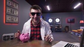 精密男性佩带的太阳镜和实验室外套讲话有猪和膝上型计算机在书桌上 影视素材