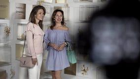 精密衣裳的两名年轻俏丽的妇女摆在摄影师 影视素材