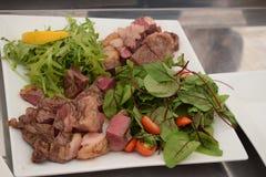 精心烹制的肉用草本和蕃茄在板材 库存照片