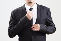 精明的商人在与工作的开始前调整他的领带 图库摄影