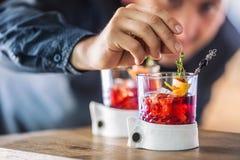 精确地准备与果子和草本装饰的侍酒者鸡尾酒饮料 准备酒精饮料的仅侍酒者手 库存照片