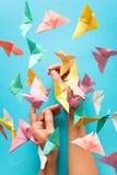 精神健康概念 五颜六色的纸蝴蝶飞行和坐妇女` s手 和谐情感 origami 纸裁减样式 免版税库存照片