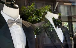 精神商店窗口剪裁显示2个时装模特的商店在无尾礼服 库存照片