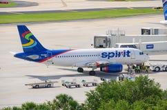 精神在机场搭乘桥梁的航空公司飞机 免版税库存照片