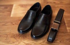 精神套黑皮鞋和传送带 库存图片