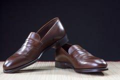 精神鞋类概念 在秸杆表面安置的对时髦的布朗便士游手好闲者鞋子 库存图片
