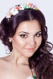 精美典雅的美丽的有长的黑发的schaslivo微笑的妇女卷曲与颜色的一个色的外缘在一件明亮的礼服的 免版税库存照片