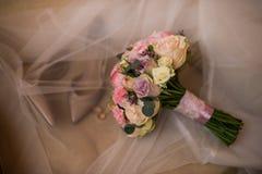 精美在淡色口气的婚礼新娘花束经典形状与玫瑰 婚姻floristry 新娘鞋子和圆环在focu外面 图库摄影