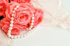 精美女性题材 桃红色珊瑚玫瑰趋向在一条淡粉红的胸罩和珍珠项链的颜色在白色背景 顶视图 关闭 免版税库存图片