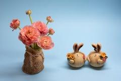 精美桃红色毛茛和野兔小雕象逗人喜爱的花束在蓝色背景 免版税库存照片