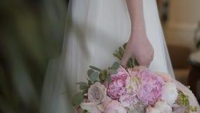精美桃红色牡丹美丽的婚姻的花束的特写镜头在新娘的手上一象牙婚纱的