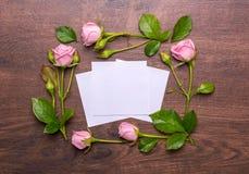 精美花圆的框架  在木背景的桃红色玫瑰 与空的地方的纸文本的 免版税库存照片