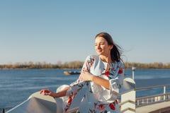 精美蓝色礼服身分在海滩和享受的日落年轻时髦的妇女 免版税库存照片