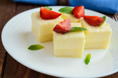 精美酸奶干酪和乳脂状的蛋白牛奶酥以立方体的形式,装饰用薄荷叶和新鲜的草莓 库存图片