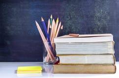 精装书和课本堆积与在桌上的铅笔在b 库存照片