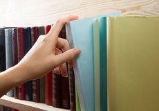 精选从一个书架的妇女书在图书馆里 回到学校 免版税库存图片
