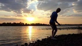 精采投掷在河水的日落和一个人平的石头在Slo Mo 股票录像