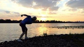 精采投掷在河水的日落和一个人平的石头在Slo Mo 影视素材