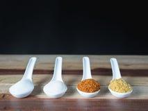 糖、盐、胡椒和被油炸的大蒜在一把白色匙子被安置 并且背景是黑的 免版税库存照片