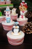 糖圣诞节在松饼的企鹅小雕象 免版税库存图片