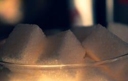 糖在玻璃花瓶的立方体特写镜头在阳光下 图库摄影