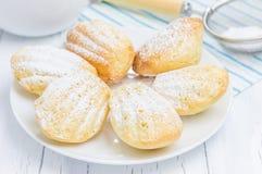 糖在白色板材的搽粉的madeleines 免版税库存图片