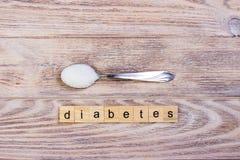 糖尿病块木信件和糖堆在匙子 免版税库存照片