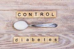 糖尿病控制块木信件和糖堆在匙子 库存照片