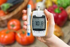 糖尿病膳食和健康吃概念 Glucometer和菜 免版税库存图片