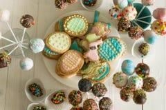 糖果、蛋糕流行音乐和曲奇饼的分类在木桌上在 免版税库存照片