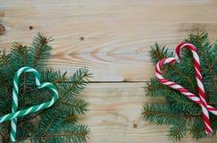 糖果与拷贝空间的锥体和圣诞树分支的绿色和红色心脏在中心 新年或情人节甜点 库存图片